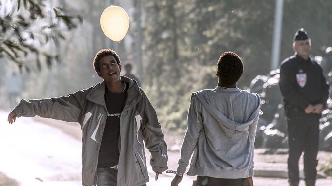 Des adolescents jouent avec un ballon, alors qu'un policier surveille les opérations