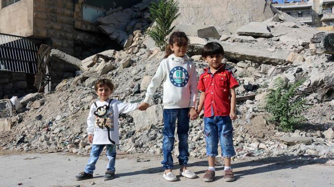 La fillette pose en compagnie de ses deux frères devant des gravats à Alep, le 10 octobre.