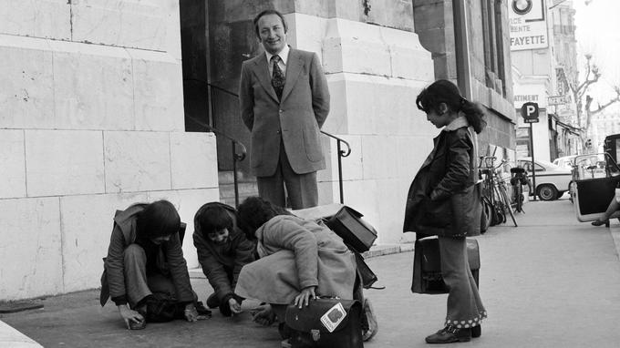 Une photo prise le 4 mars 1974 à Nice montre l'écrivain français Joseph Joffo devant des enfants jouant aux billes.
