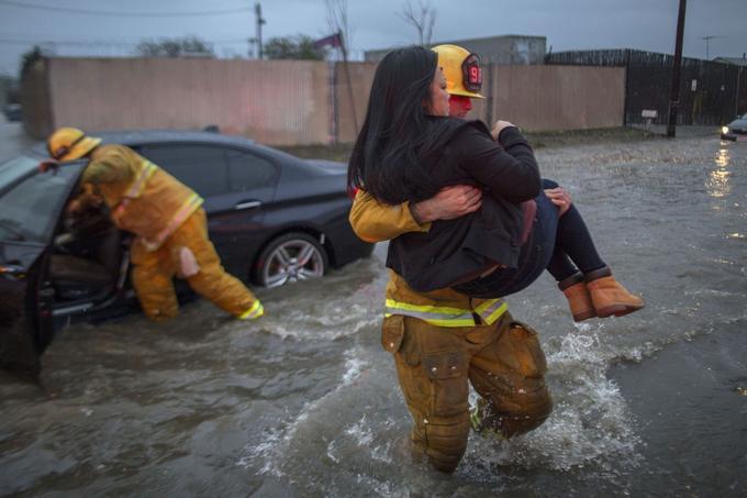 Un pompier porte une femme dont la voiture est bloquée par les inondations.