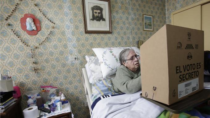 À Quito, une équatorienne âgée enregistre son vote grâce à un système de vote à domicile prévu pour les handicapés.