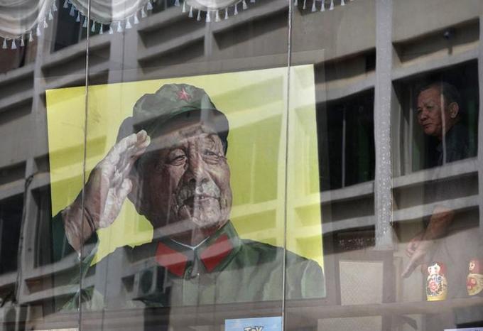 Un Chinois regarde par la fenêtre où se reflète un portrait de Deng Xiaoping en uniforme militaire, à Shenzhen, dans le sud de la Chine.