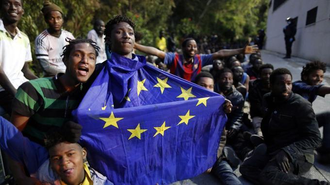 Un homme arbore le drapeau européen au milieu d'un groupe qui exprime sa joie après avoir franchi la frontière de l'enclave de Ceuta, lundi 17 février.