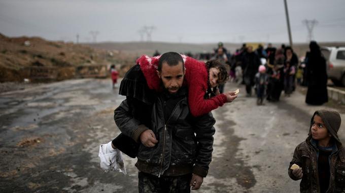 Un irakien qui a quitté sa maison à Mossoul porte sa fille sur le dos, le 3 mars.