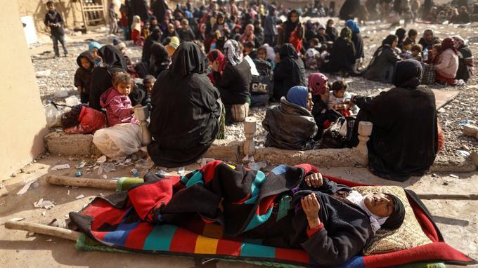 Des personnes venues de Mossoul attendent un contrôle de sécurité non loin d'une base de l'armée irakienne, le 27 février.