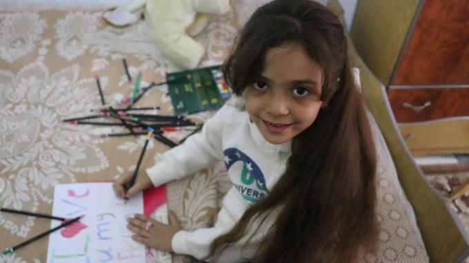 Bana dessine un message adressé à ceux qui la suivent à travers le monde, en octobre 2016, à Alep.