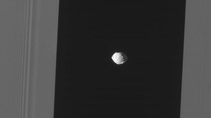 Sur cette image prise le 7 mars par la sonde Cassini, Pan est encadré à gauche et à droite par les anneaux de Saturne (en gris).