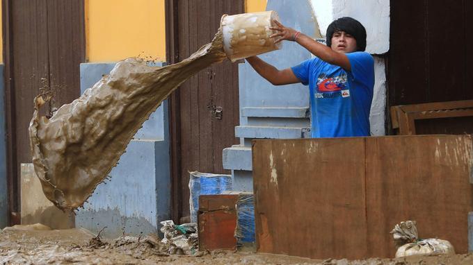 Un jeune habitant de Trujillo écope la boue devant sa maison, à Trujillo, le 18 mars.