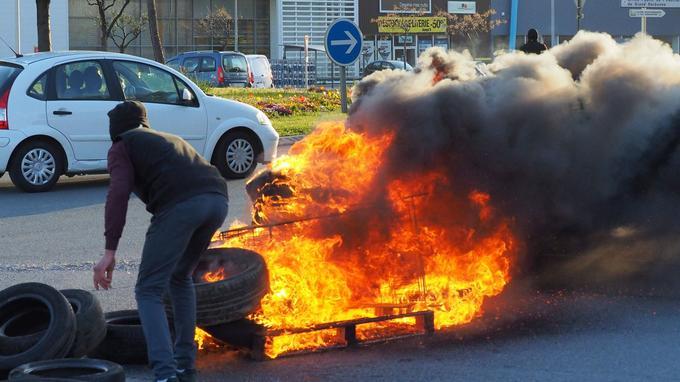 Un manifestant tente de bloquer l'accès d'une route avec un pneu brûlé.