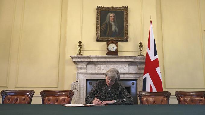 La première ministre britannique Theresa May signant la lettre déclenchant le Brexit, hier à Londres.