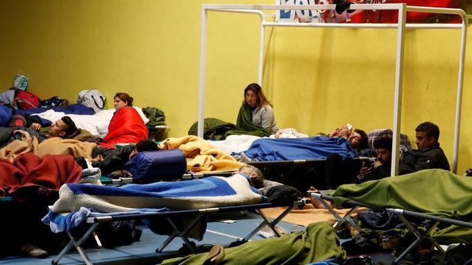 Des migrants se reposent dans un gymnase après l'incendie du camp de Grande-Synthe.