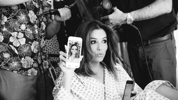 Eva Longoria se repose pendant qu'on la coiffe: elle sort ses téléphones et se met à jouer différentes applications tout en faisant d'amusantes grimaces.Crédits photo: Gareth Cattermole/ Getty Images for L'Oreal Paris