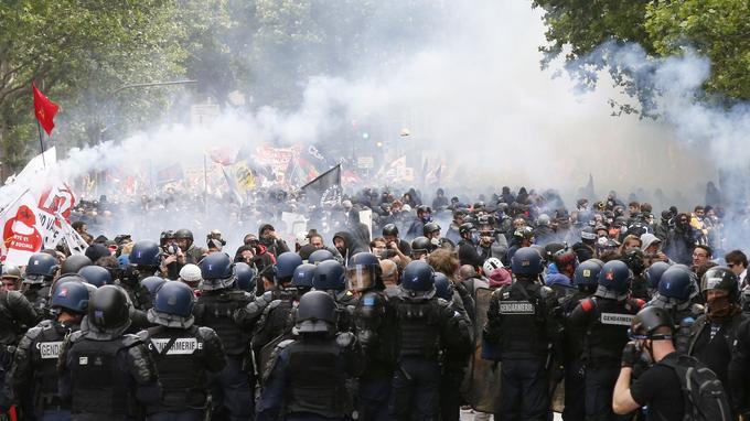 Du gaz lacrymogène flotte au-dessus de manifestants qui font face aux forces de l'ordre, à Paris, le 14 juin 2016, dans le cadre du conflit autour de la loi Travail.