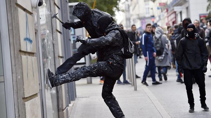 Un manifestant s'attaque à la vitrine d'une banque en marge d'une manifestation contre la loi Travail à Nantes, le 17 mars 2016.