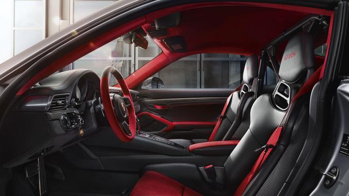 L'habitacle typé course adopte des sièges baquets en coque carbone drapés de suédine rouge.