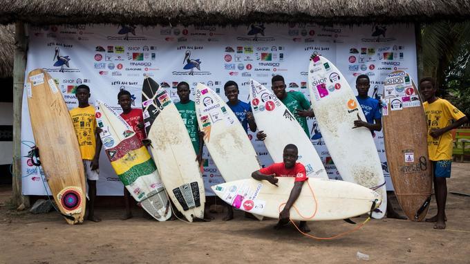 De jeunes surfeurs posant avec leur planche.