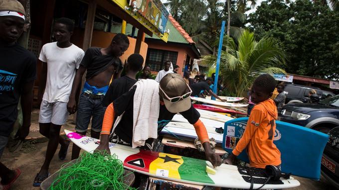 Des participants lavant leur planche de surf avant la compétition.