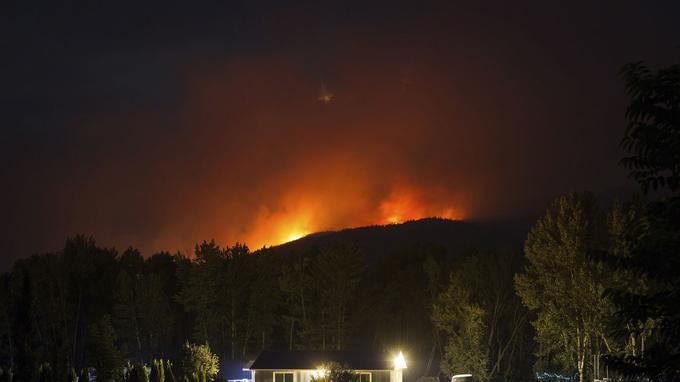 Les flammes illuminent Cache Creek, en Colombie Britannique. (Crédit photo: Darryl Dyck / The Canadian Press via AP)