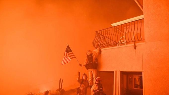 Des pompiers récupèrent un drapeau sur le mur d'une maison d'Oroville, en Californie. (Crédit photo: Josh Edelson / AFP)