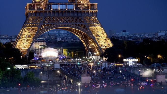 Des badauds réunis derrière le cordon de sécurité au pied de la tour Eiffel alors que les couples Macron et Trump partagent un dîner, le 13 juillet.