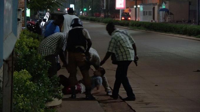 Un homme blessé est évacué par des hommes en arme à Ouagadougou.