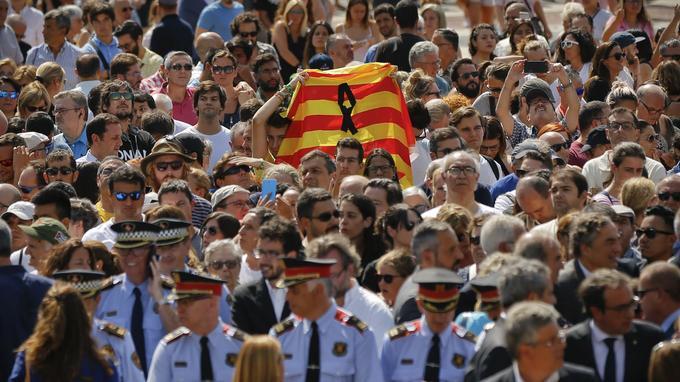 Le drapeau de la Catalogne flotte dans la foule.Dans la foule venue se recceuillir, une pancarte «Barcelone reste unie face au terrorisme