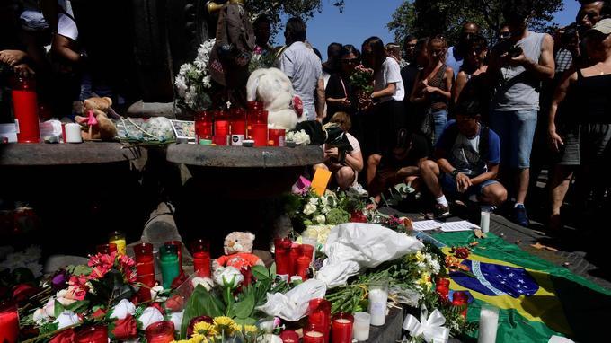Des personnes sont venues déposer des bougies, messages et fleurs à la fontaine de Canaletes sur les ramblas.