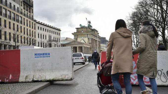 Les gens passent entre des blocs de béton près de la porte de Brandebourg à Berlin à la veille des festivités du nouvel an, en Allemagne, le jeudi 29 décembre 2016.