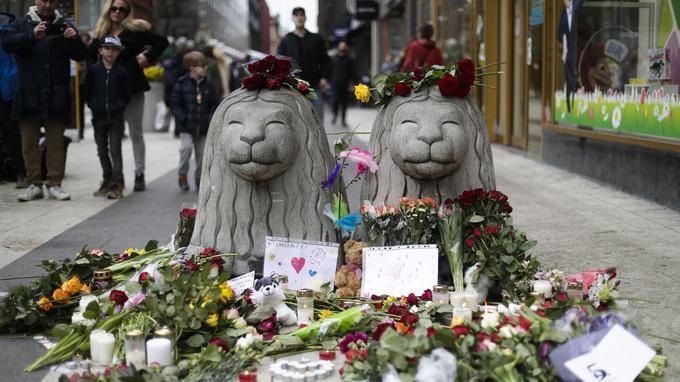 Des fleurs près des lions en pierre sur les lieux de l'attentat, une des principales rues commerçantes de la ville à Stockholm, en Suède, le dimanche 9 avril 2017.