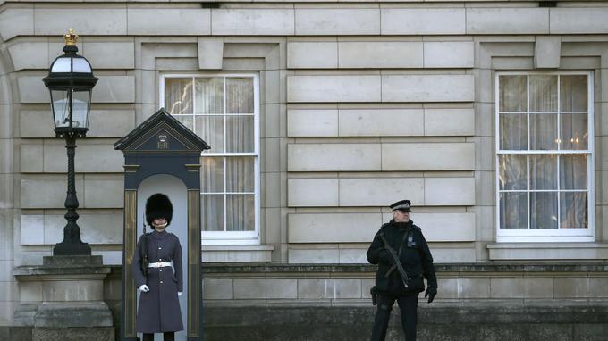 Un officier de police armé se tient aux côtés d'un membre de la Garde royale au Palais de Buckingham, à Londres.