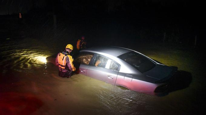 Des équipes de secours inspectent une voiture en zone inondée à Fajardo, mercredi.