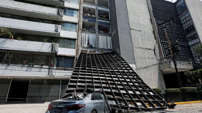 La façade d'un immeuble effondrée sur une voiture en contrebas.