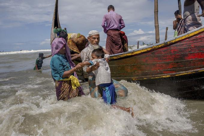 Un homme aide un enfant à descendre d'un bâteau tout juste arrivé de Birmanie.