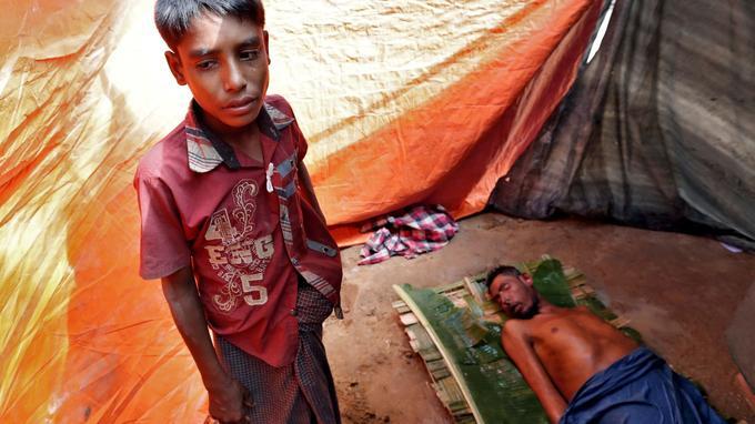 Un enfant réfugié aux côtés de son père, dans le camp de Cox's Bazar.