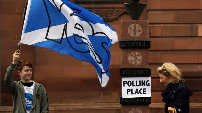 Un partisan de l'indépendance de l'Écosse agite le drapeau écossais orné d'un «oui», le 18 septembre 2014, jour du référendum sur l'indépendance écossaise.