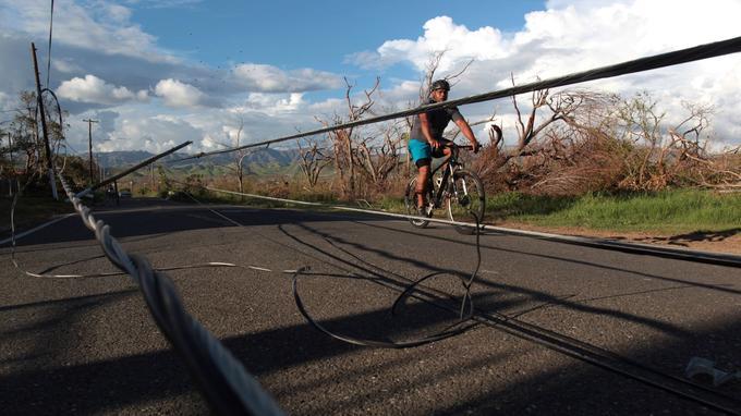 Un homme fait du vélo à côté de débris de fils électriques à Salinas, à Porto Rico.