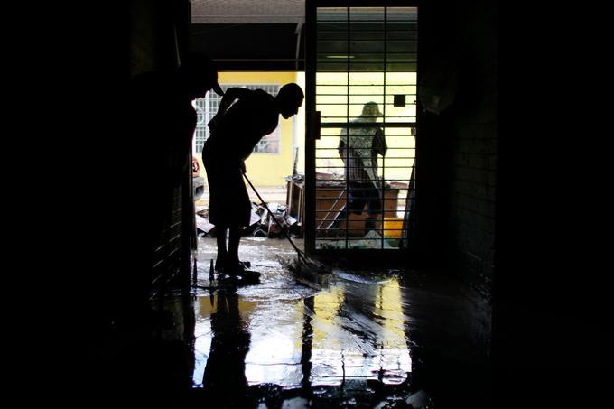 Des commerçants de Comeiro, à Porto Rico, enlèvent la boue de leur magasin.