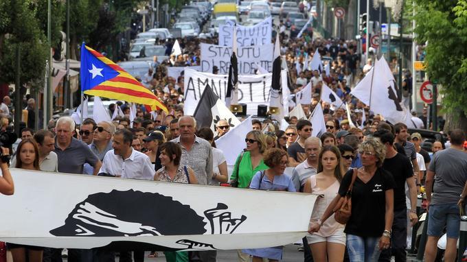 Des manifestants participent au rassemblement organisé par «Ghjuventu Indipendentista» («Jeunesse indépendantiste»), en 2015 à Ajaccio, pour demander un statut particulier pour les résidents de l'île. À gauche, on aperçoit un drapeau catalan indépendantiste.
