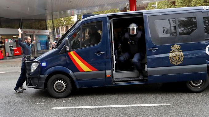 Un manifestant empêche un fourgon de police d'avancer à Barcelone.