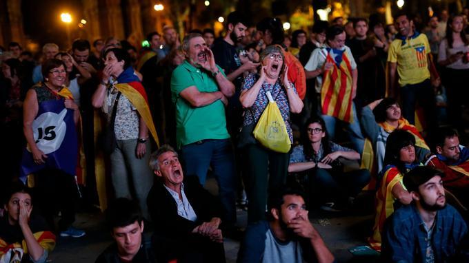 Des partisans de l'indépendance venus suivre le discours de Carles Puigdemont adressent des huées à l'écran qui rediffuse la séance au Parlement catalan.