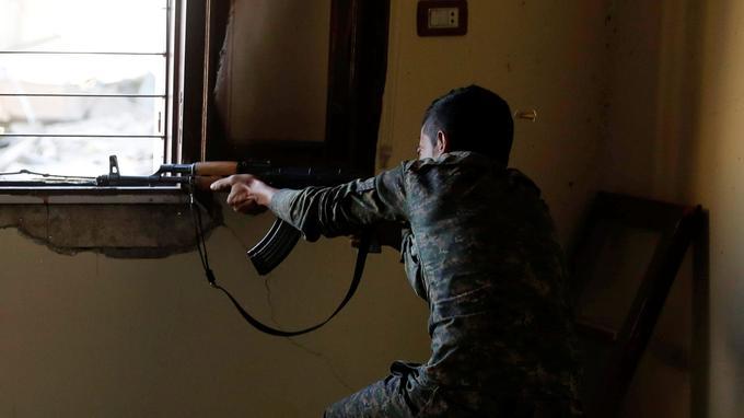 Un combattant des FDS vise l'une des positions où sont retranchés les soldats de l'Etat islamique, sur la ligne de front à Raqqa.