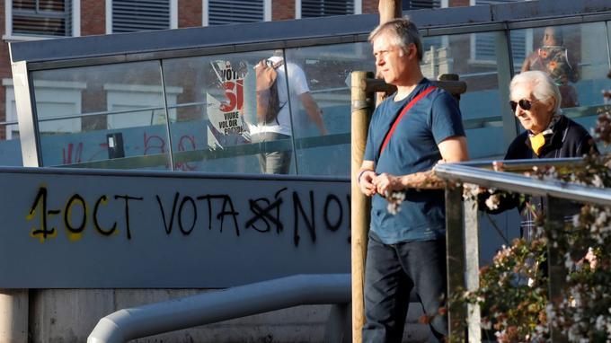«Le 1er octobre, vote non», lit-on avec ce slogan corrigé: le «oui» initial a été rayé. Au-dessus, on remarque une affiche pro-indépendance arrachée.