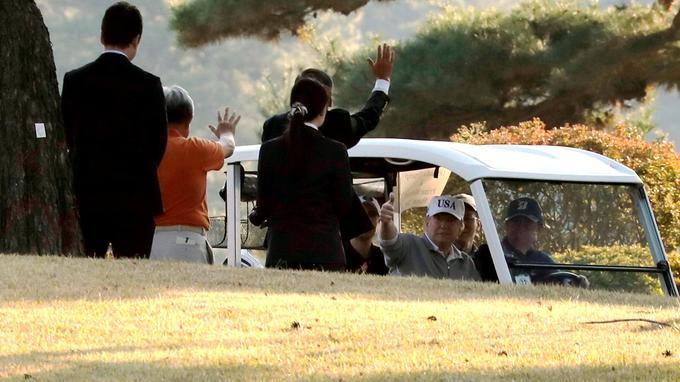 Les deux dirigeants dans une voiturette de golf.