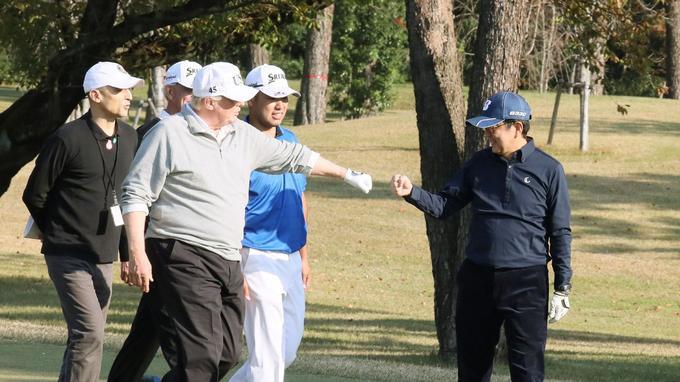 Donald Trump et Shinzo Abe échange une poignée de main sous le regard du joueur professionnel Hideki Matsuyama.