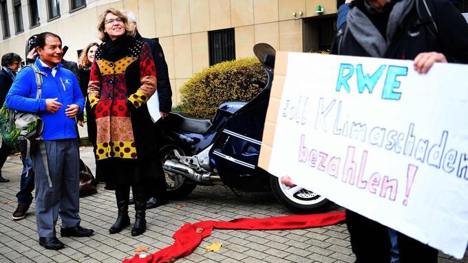 Saul Luciano Lliuya et son avocate devant le tribunal d'Essen, en 2016, avant une première décision défavorable. Un soutien du fermier brandit une pancarte: «RWE doit payer pour les dégâts climatiques».