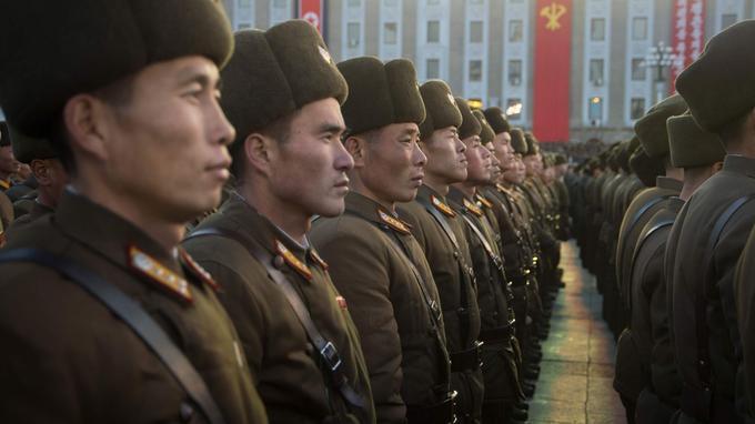 Les soldats, chapkas enfoncées sur la tête, ont le regard rivé vers la scène.