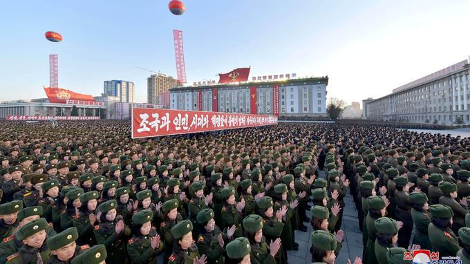 Dans les rangs de l'armée, de nombreuses banderoles à la gloire de Kim Jong-Un.