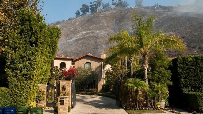 De la fumée s'élève à proximité d'une résidence du quartier de Bel Air, à Los Angeles, mercredi.