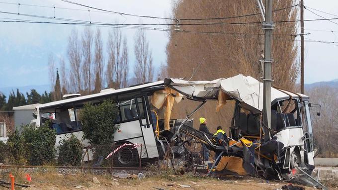 Des agents des services de remorquage s'activent autour de l'épave du bus percuté jeudi par un train régional à Millas, près de Millas, dans le sud de la France.