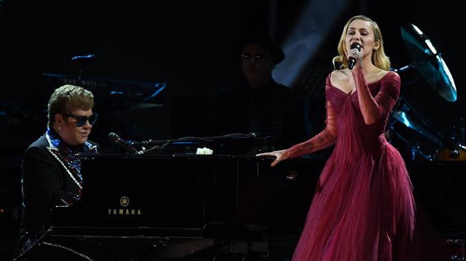 Avec une rose blanche dans son piano Yamaha pour signifier le soutien de Time's Up, Elton John a interprété sa chanson iconique 1971 «Tiny Dancer» avec Miley Cyrus.